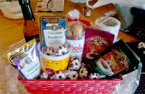Basket full of items that would be great for a coffee break - coffee, flavor, biscotti, candies