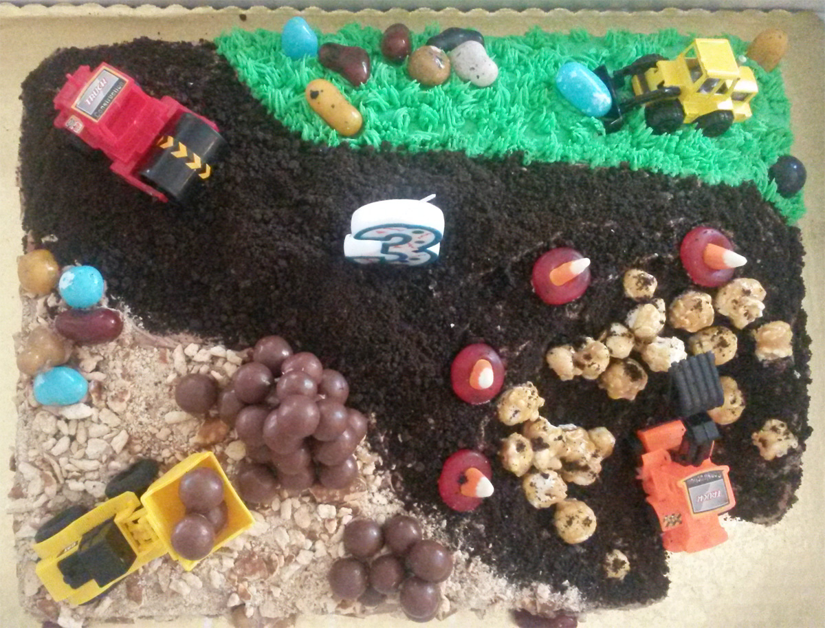 Cake made for 3 year old party with toy trucks, and chocolate goodies on the construction site