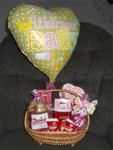 yellow ballon flies over a gift basket of biscotti and treats to celebrate birth - its a girl!