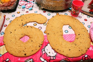 Chocolate Chip Cookies as big as your head spell out 60, On top of Hello Kitty table cloth