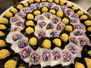 A tray of Peanut butter truffles and chocolate truffles with sprinkles of purple, pink,and white