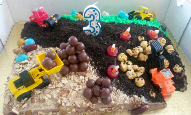 Cake made for construction theme party has crushed oreos, carmel corn rocks, and candy corn orange cones for 'danger'