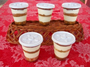 5 tiramisu cups prettily lined up on red table cloth